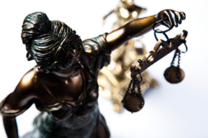 Criminal justice system illustrated by figurine holding the scales of justice.